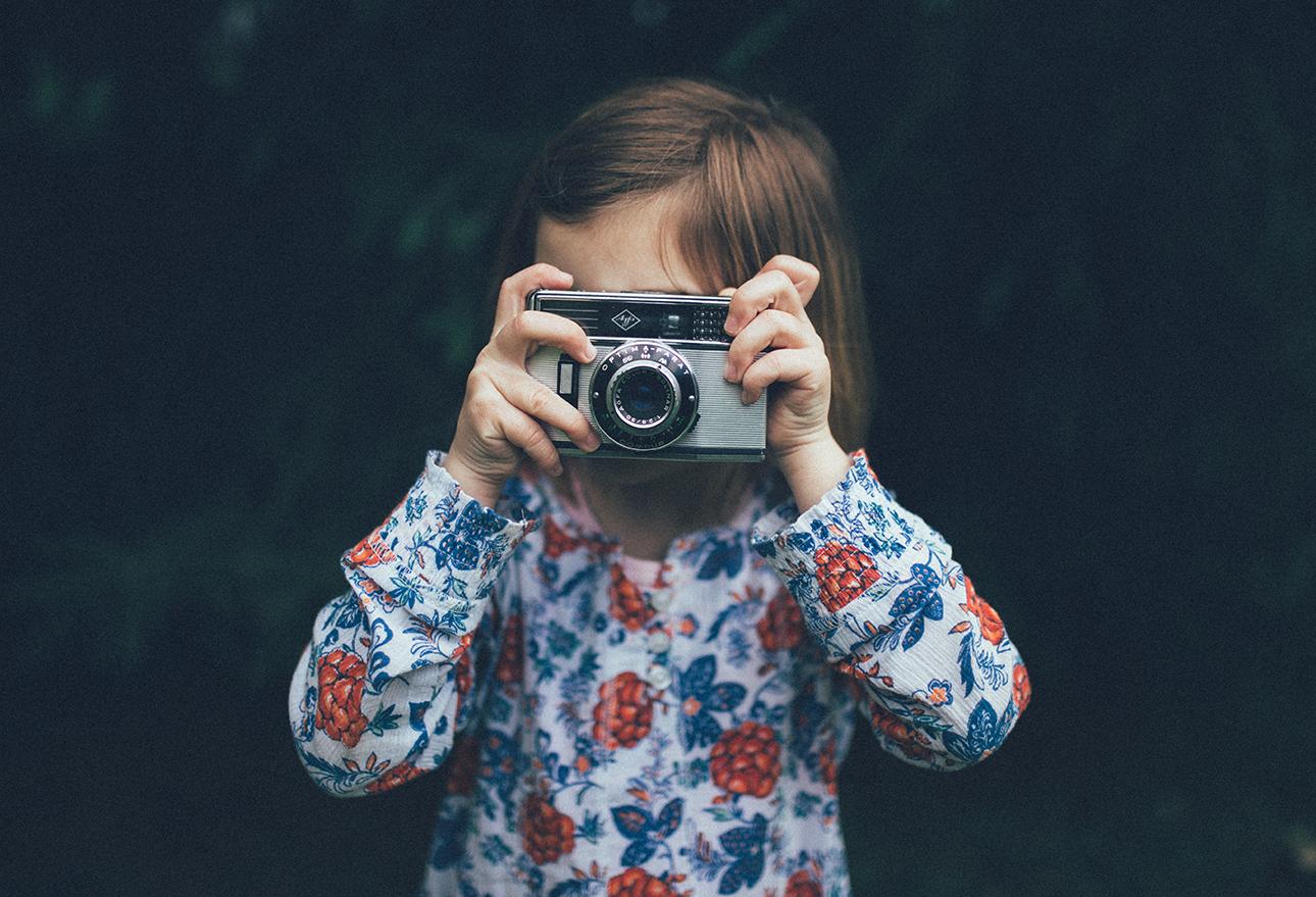 ein kleines Mädchen, das ein Foto mit einer Kamera macht
