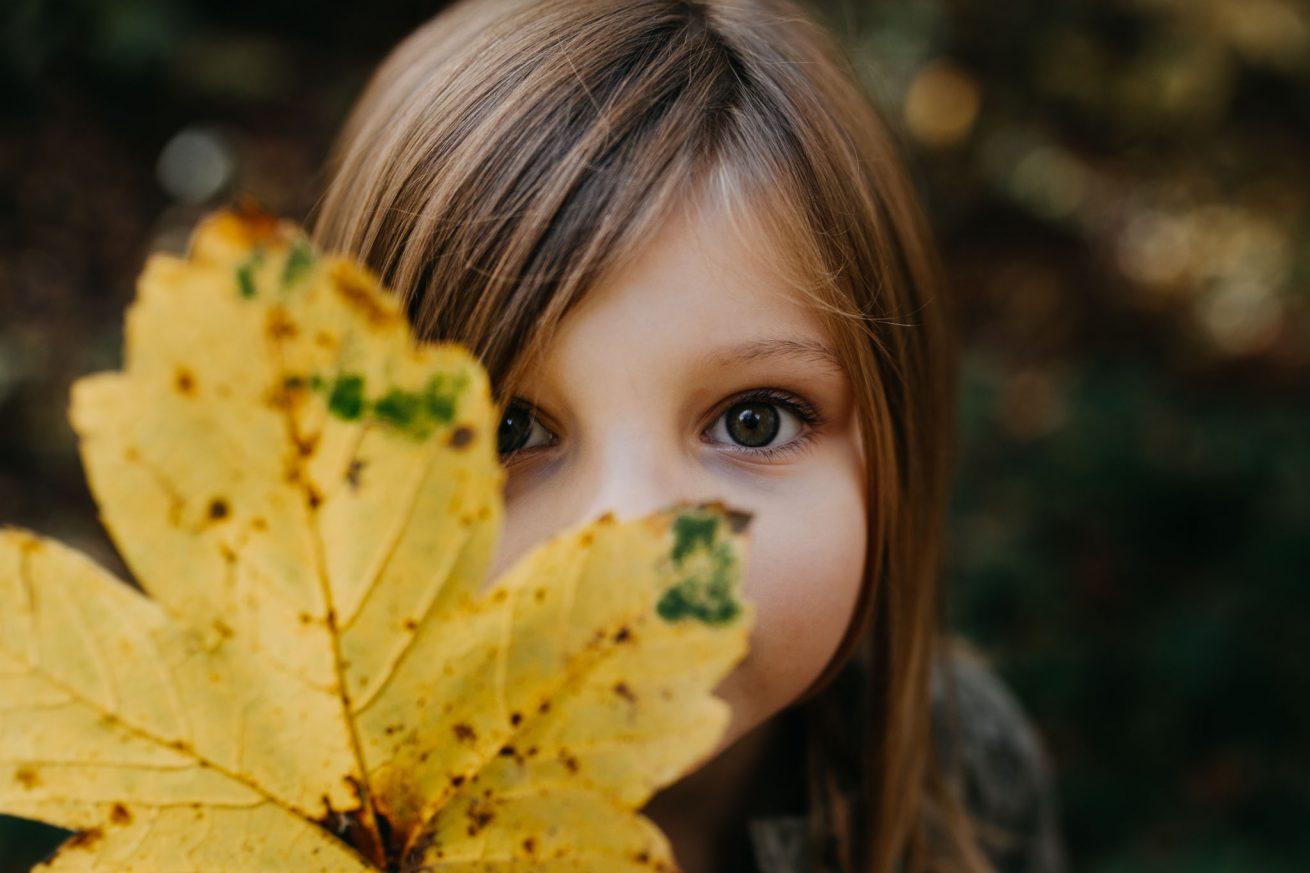 Portrait eines Mädchens, das halbe Gesicht bedeckt mit einem herbstlichen Blatt