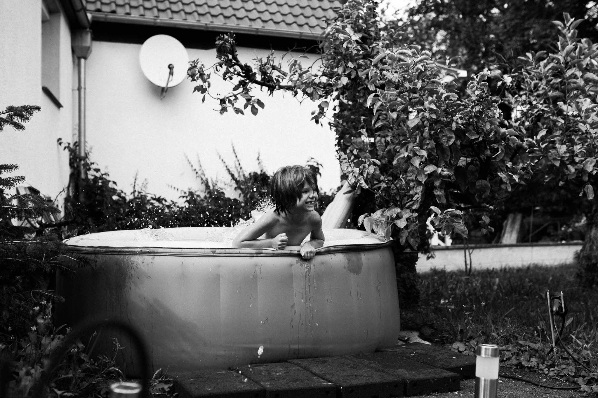 Mädchen planscht im Planschbecken im Garten