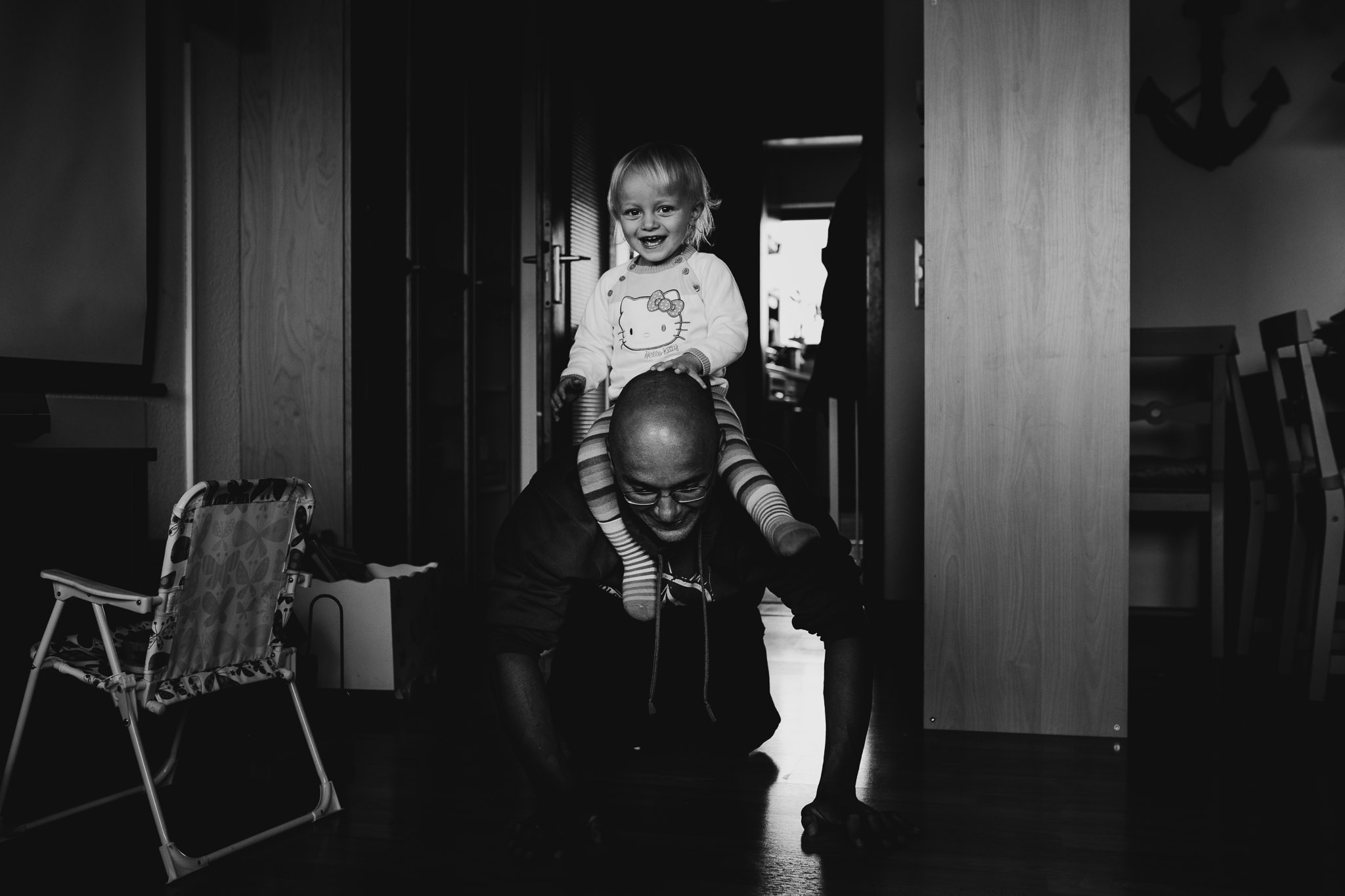 Kleines Mädchen reitet auf dem Rücken von Papa
