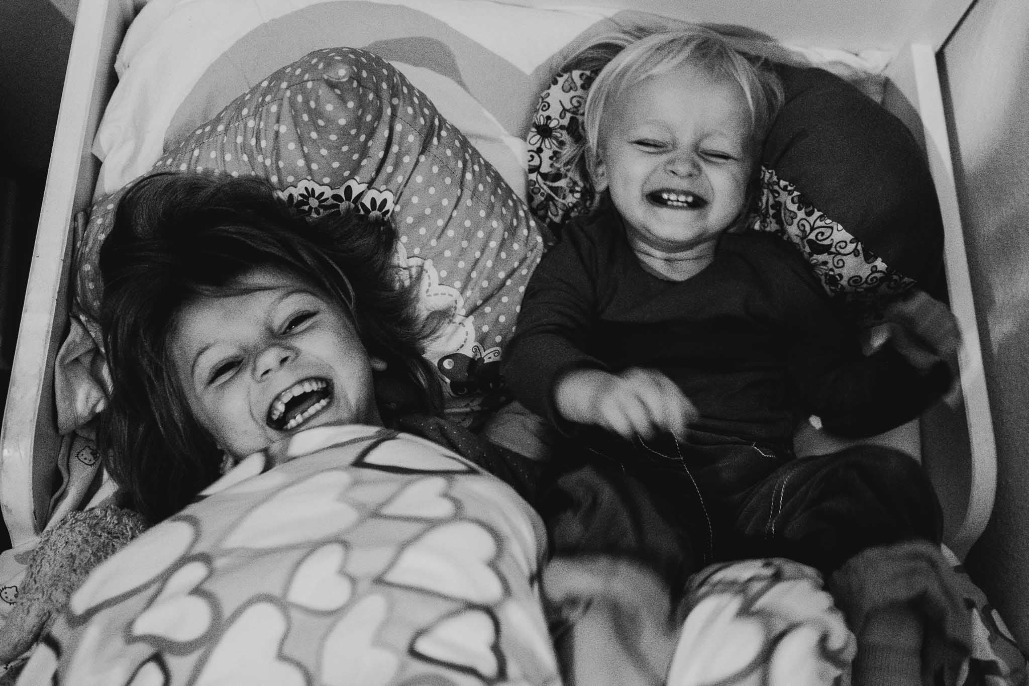 Zwei Schwestern liegen lachend im Bett