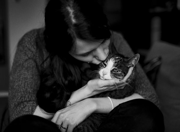 Frau hat Katze auf dem Schoß und gibt der Katze einen Kuss auf den Kopf