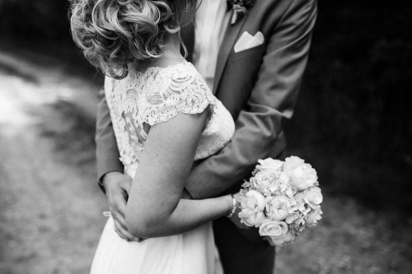 Detailaufnahme vom Oberkörper eines Brautpaares, welches sich in den Armen hält