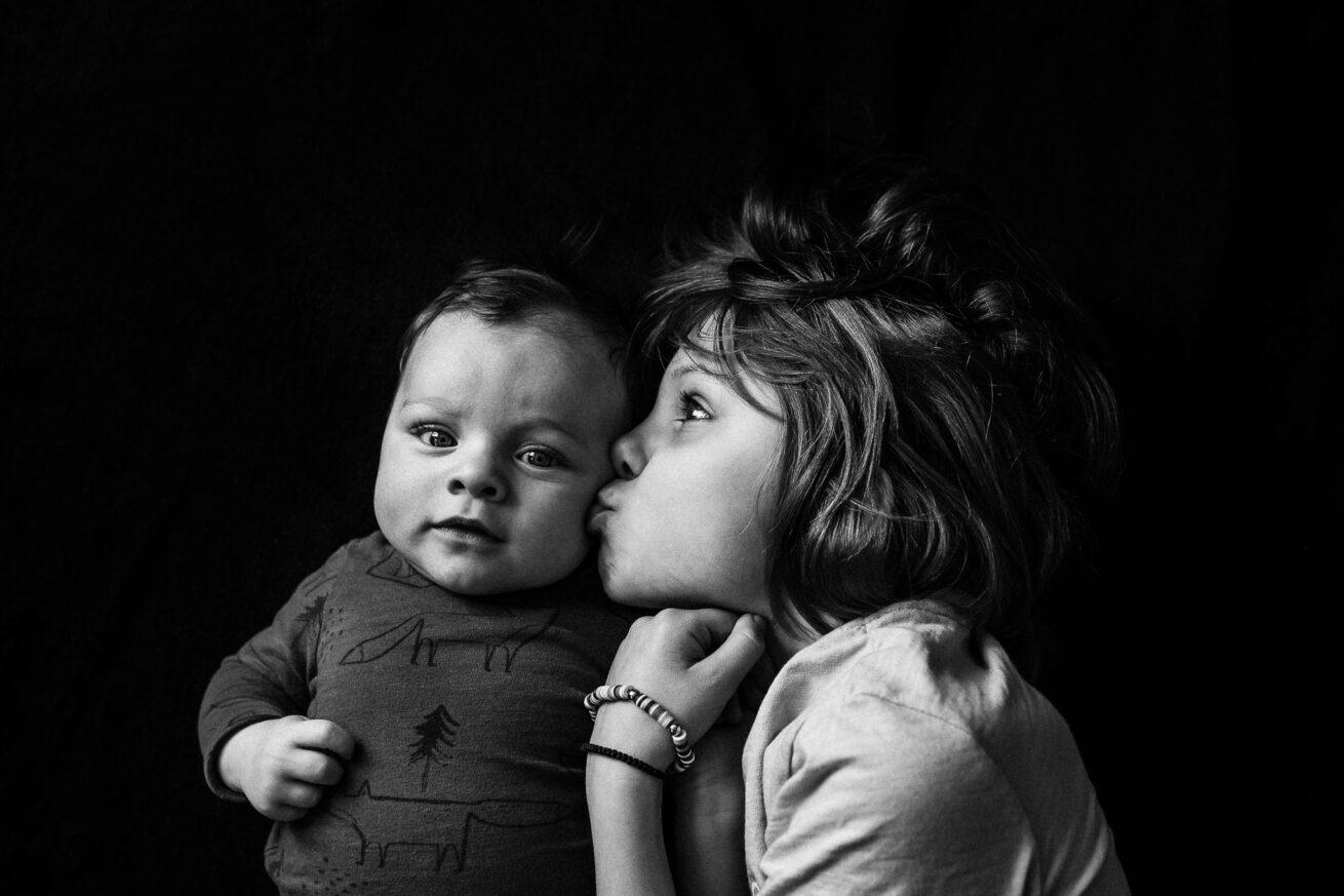 Große Schwester gibt kleinem Baby Bruder einen Kuss auf die Backe
