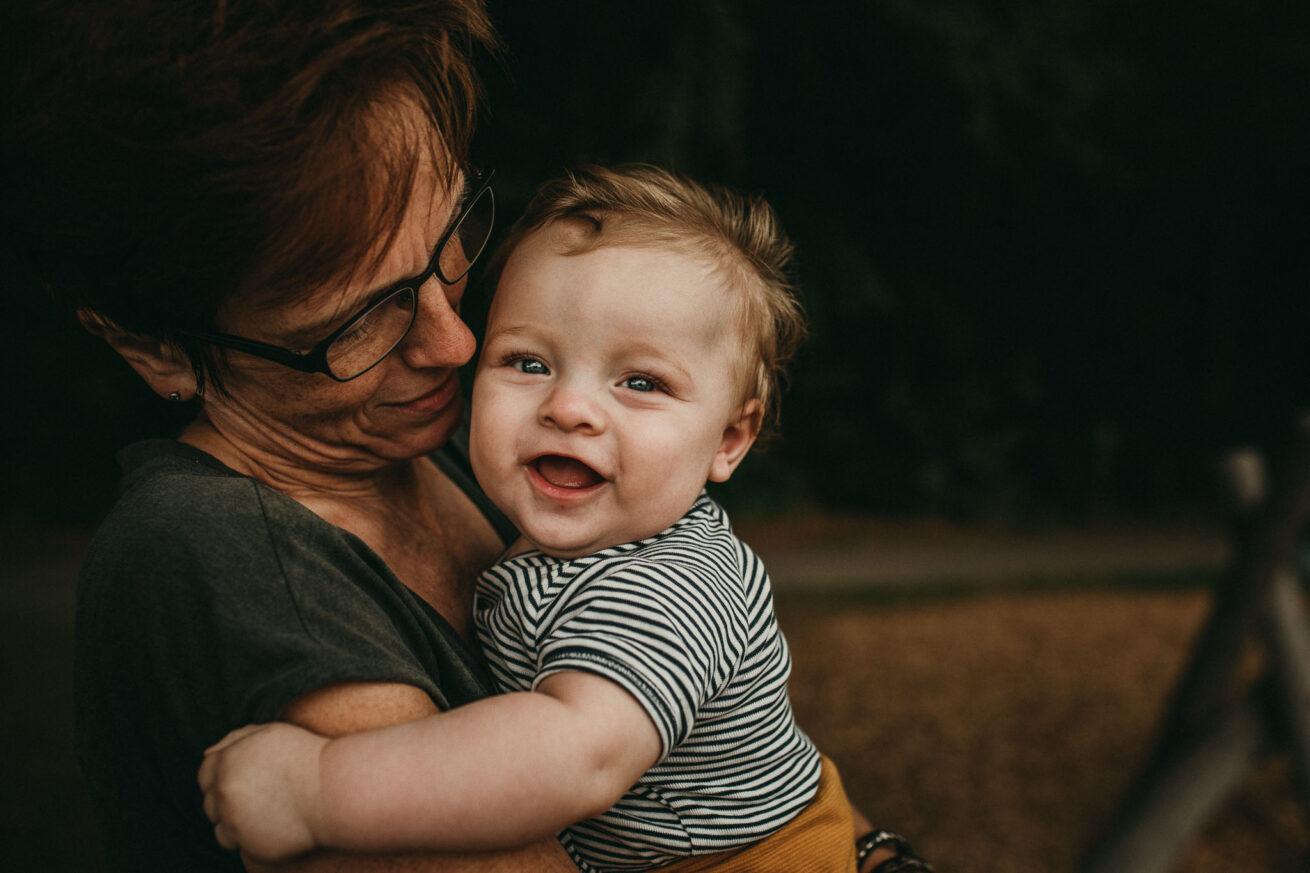 Lächelndes Baby auf dem Arm der Oma