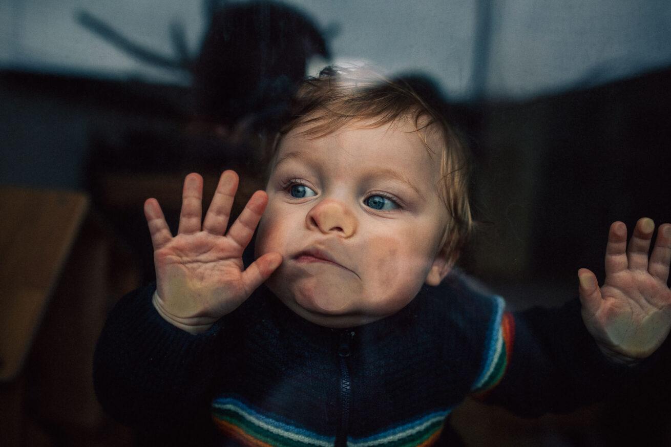 Baby klebt mit Gesicht an der Scheibe