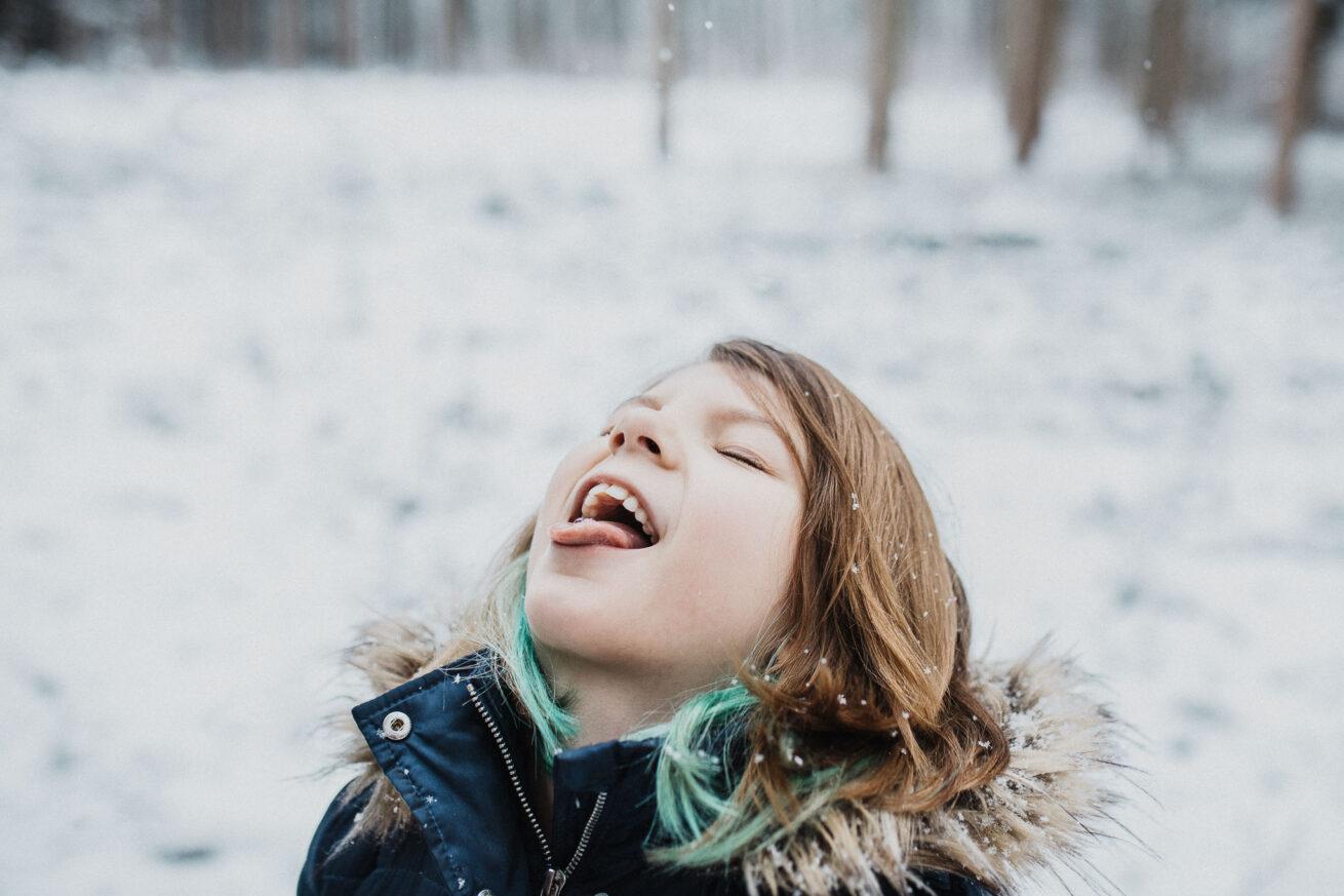 Mädchen fängt mit der Zunge Schneeflocken